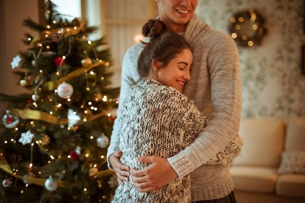 Mujer joven que abraza al hombre cerca de abeto decorado Foto gratis