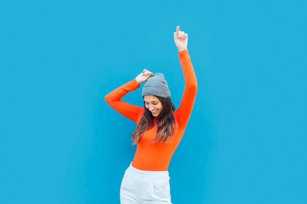 Mujer joven que baila con el brazo levantado delante de fondo azul Foto gratis