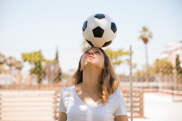 Mujer joven que balancea el balón de fútbol en la cabeza Foto gratis