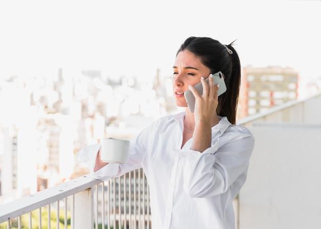 Mujer joven que se coloca en el balcón que sostiene la taza de café que habla en el teléfono móvil Foto gratis