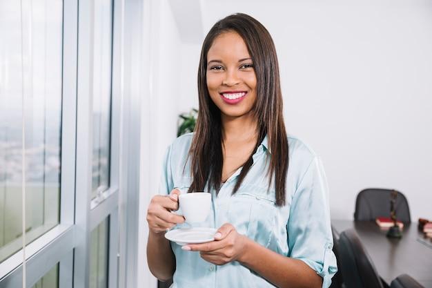 Mujer joven que se coloca con la taza de café en oficina Foto gratis