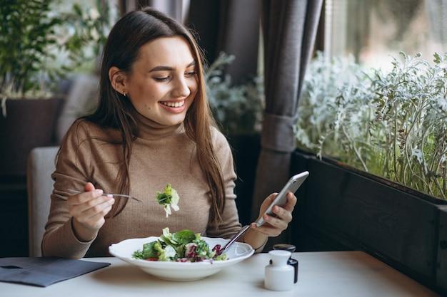 Mujer joven que come la ensalada en un café Foto gratis
