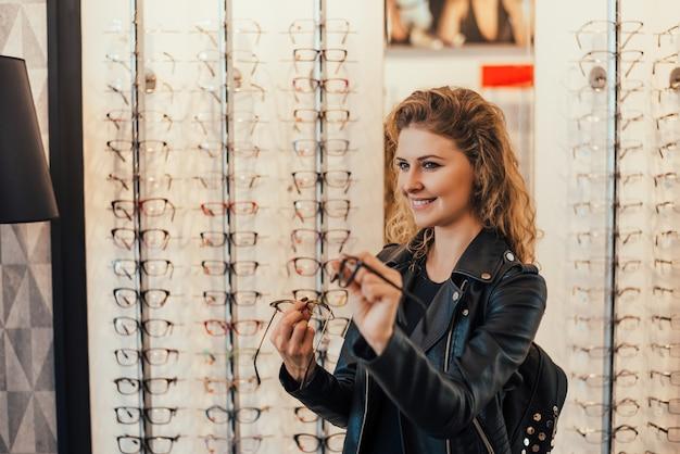 Mujer joven que compra nuevos vidrios en la tienda del óptico. Foto Premium