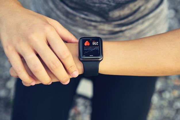 Mujer joven que controla el reloj deportivo que mide la frecuencia cardíaca y el rendimiento después de correr. Foto Premium