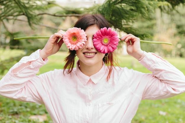Mujer joven que cubre ojos flores y sonriendo Foto gratis