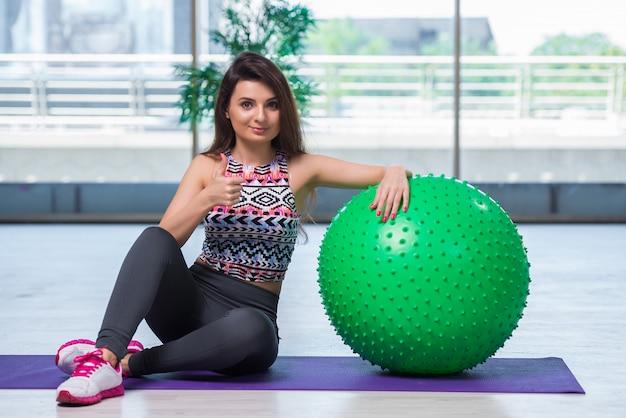 Mujer joven que ejercita con la bola suiza en concepto de la salud Foto Premium