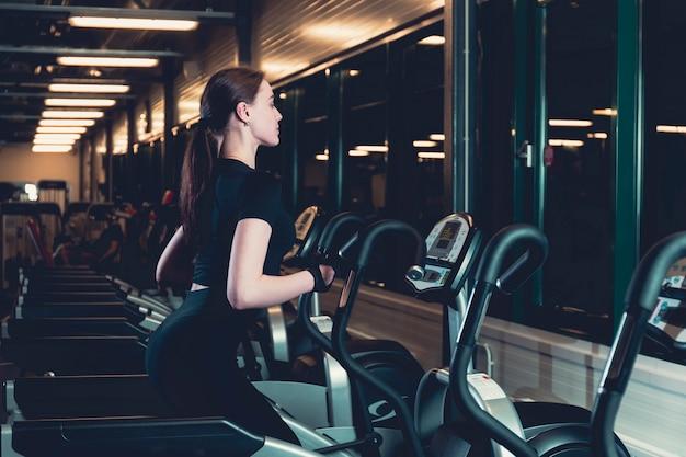 Mujer joven que ejercita en la máquina cardio elíptica Foto gratis
