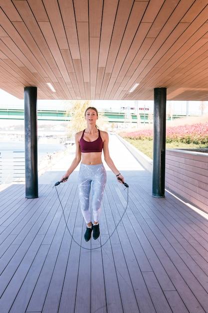Mujer joven que ejercita usando la cuerda que salta en aptitud Foto gratis