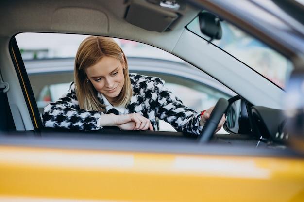 Mujer joven que elige un coche en una sala de exposición de automóviles Foto gratis