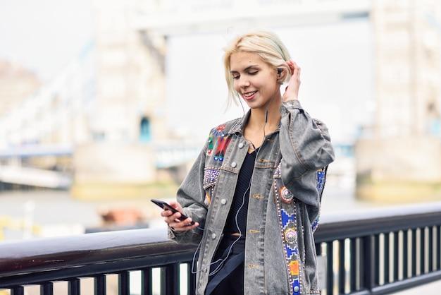 Mujer joven que escucha la música en fondo urbano. Foto Premium