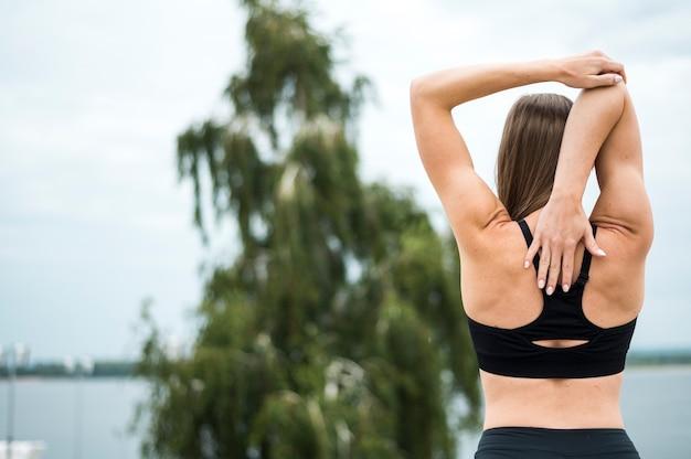 Mujer joven que estira en el tiro medio del parque Foto gratis