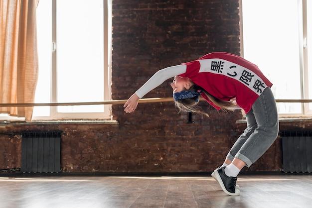 Mujer joven que se extiende hacia atrás en el estudio de danza Foto gratis