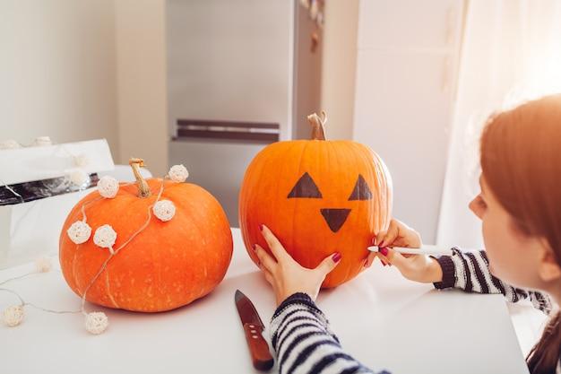 Mujer joven que hace la jack-o-linterna para halloween en cocina. dibujando ojos, nariz y boca con bolígrafo sobre calabaza Foto Premium