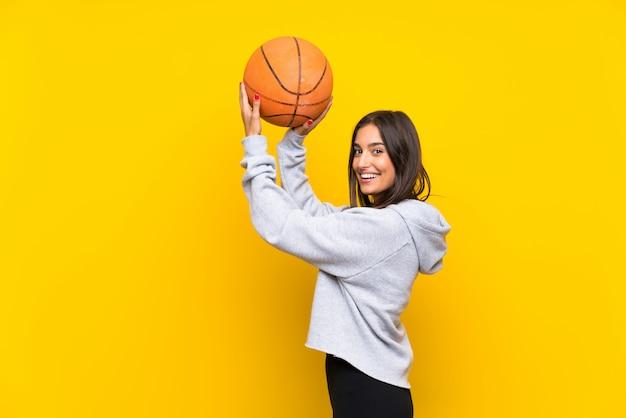Mujer joven que juega a baloncesto sobre la pared amarilla aislada Foto Premium