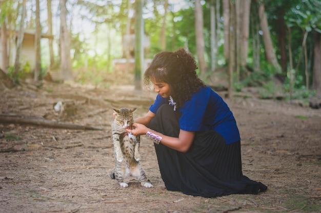 Mujer joven que juega con el gato en el bosque en el campo de tailandia Foto Premium