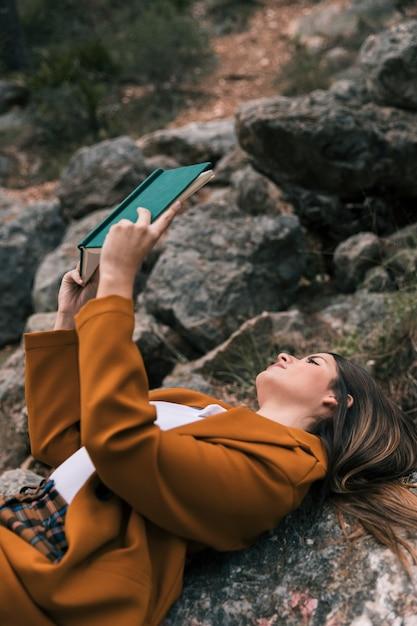 Mujer joven que miente en la roca que lee el libro Foto gratis