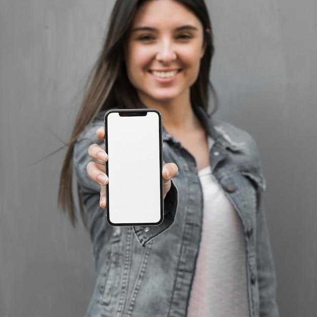 Mujer joven que muestra smartphone en la mano Foto gratis