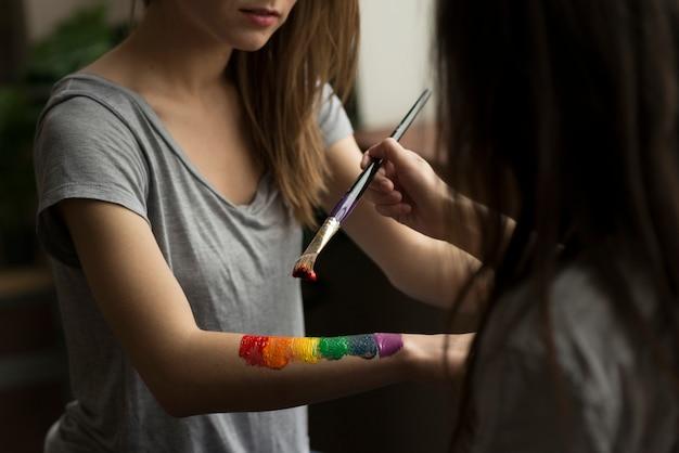 Mujer joven que pinta la bandera del arco iris sobre la mano de su novia con pincel Foto gratis