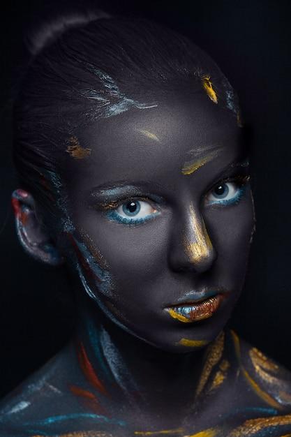 Mujer joven que posa cubierta con pintura negra Foto gratis