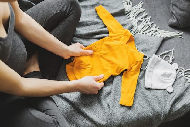 Mujer joven que prepara la ropa para el bebé Foto gratis