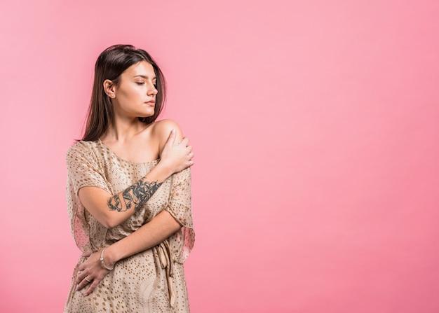 Mujer joven que presenta en vestido con el hombro desnudo Foto gratis