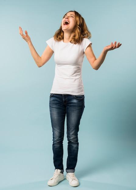 Mujer joven que ríe ruidosamente contra fondo azul Foto gratis