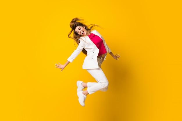 Mujer joven que salta sobre la pared amarilla aislada Foto Premium