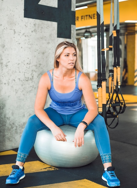 Mujer joven que se sienta en bola de la aptitud en gimnasio Foto gratis