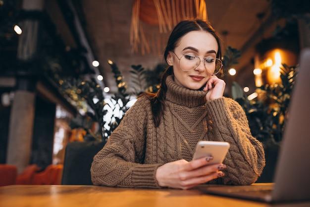 Mujer joven que se sienta en café y que trabaja en la computadora portátil Foto gratis