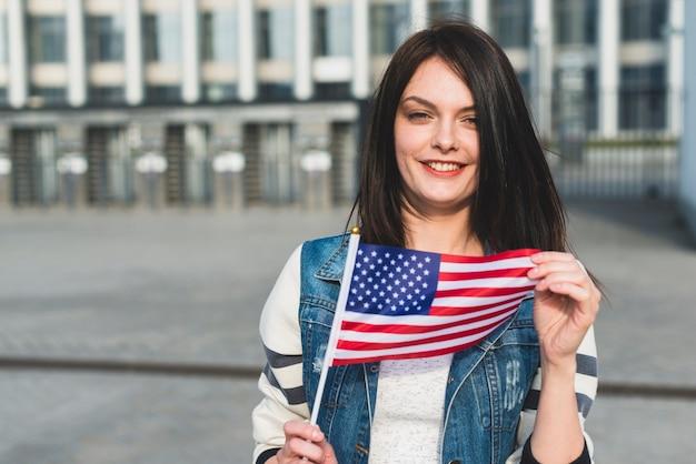Mujer joven que sostiene la bandera estadounidense en el día de la independencia Foto gratis