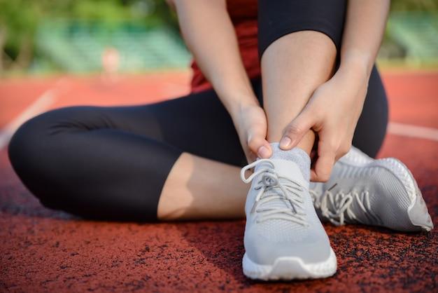 Mujer joven que sostiene el tobillo en dolor en la pista del estadio. Foto Premium