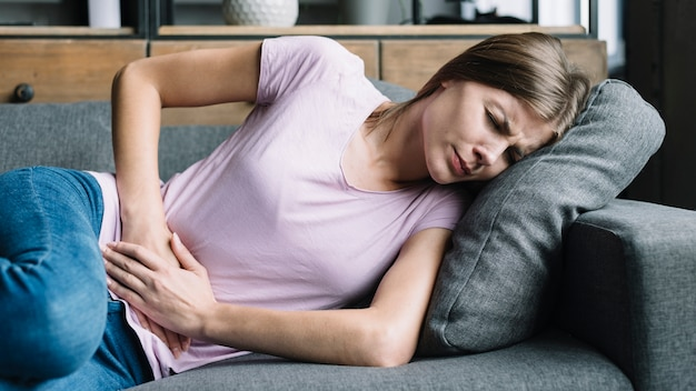 Mujer joven que tiene dolor de estómago que miente en el sofá Foto Premium