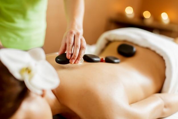 Mujer joven que tiene una terapia de masaje con piedras calientes Foto Premium