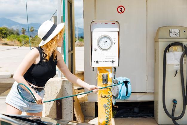 Mujer joven que toma la herramienta para llenar los neumáticos de coche con aire Foto gratis