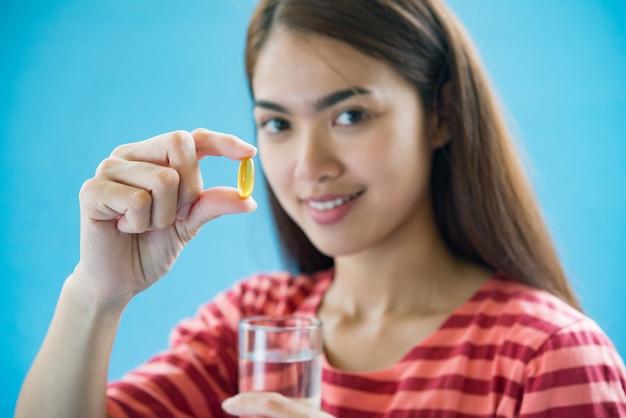 Mujer joven que toma la píldora de la medicina después de la orden del doctor Foto gratis