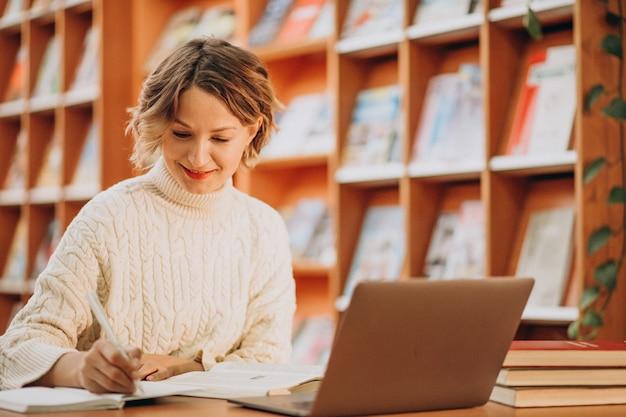 Mujer joven que trabaja en la computadora portátil en una biblioteca Foto gratis