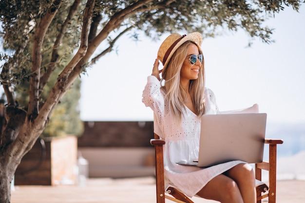 Mujer joven que trabaja en la computadora portátil en vacaciones Foto gratis