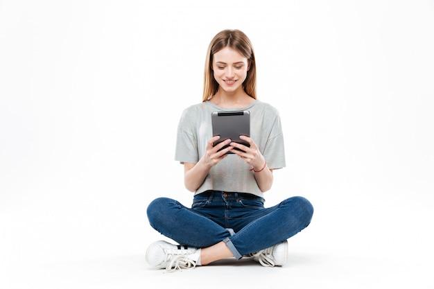 Mujer joven que usa la tableta aislada Foto gratis