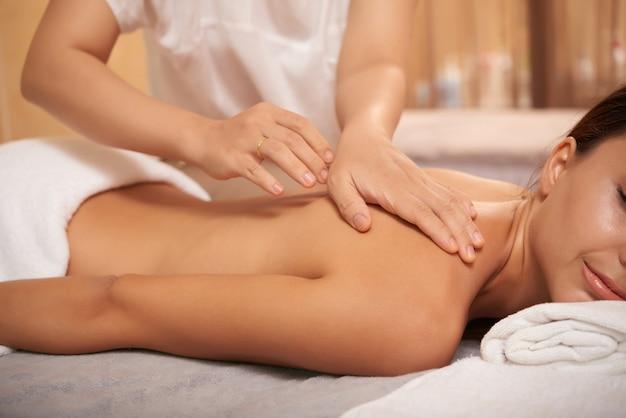 Mujer joven recibiendo masaje de espalda en el salón de spa Foto gratis