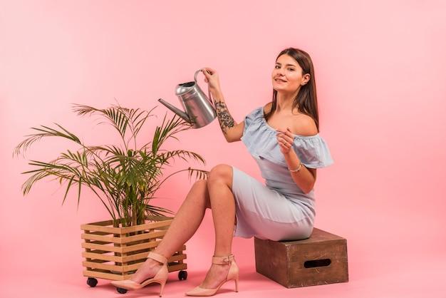 Mujer joven con regadera cerca de planta de interior Foto gratis