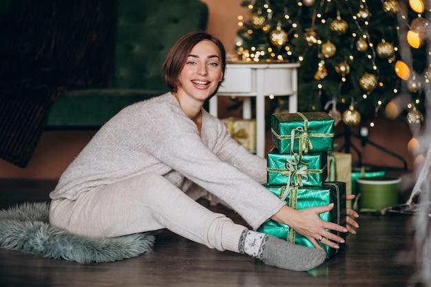 Mujer joven con regalo de navidad junto al árbol de navidad Foto gratis