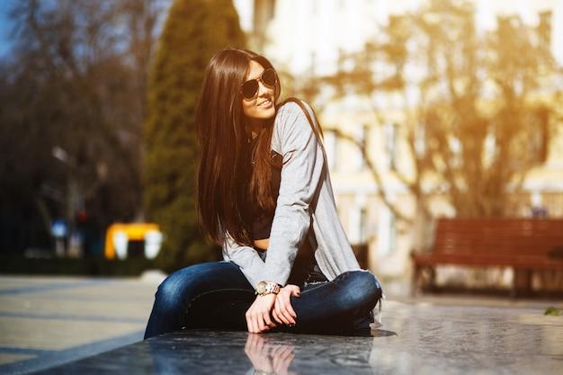 Mujer joven relajada en la plaza Foto gratis
