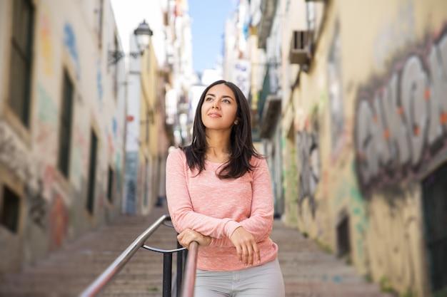 Mujer joven relajada que se inclina en la barandilla de las escaleras de la ciudad Foto gratis