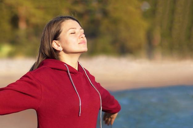 Mujer joven relajada respira aire fresco en la naturaleza en la playa Foto Premium