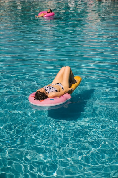 Mujer joven relajando en flotador en piscina   Descargar Fotos gratis