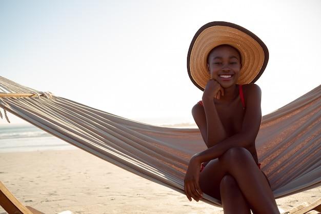 Mujer joven relajándose en una hamaca en la playa Foto gratis