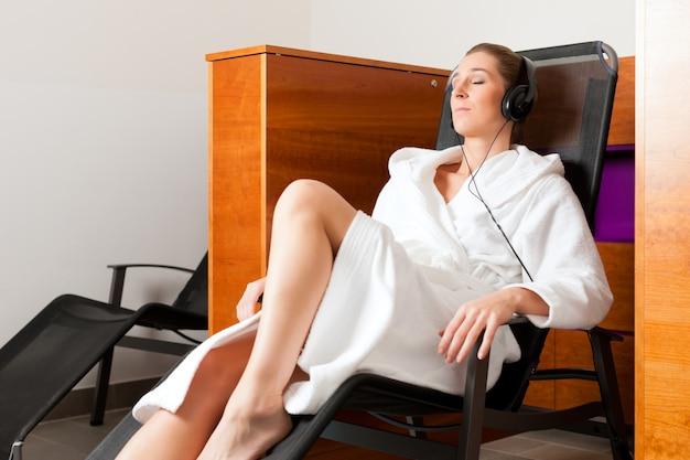 Mujer joven relajante en spa con música Foto Premium