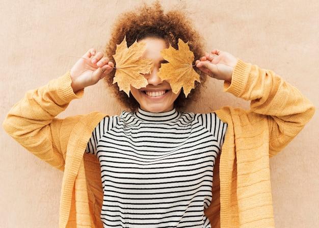 Mujer joven rizada que cubre sus ojos con hojas Foto gratis