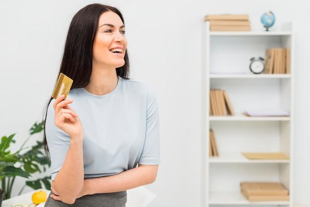 Mujer joven en la ropa azul que se coloca con la tarjeta de crédito en oficina Foto gratis
