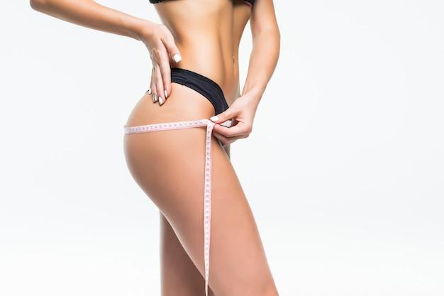 Mujer joven en ropa interior negra que mide su cintura con cinta métrica. Foto gratis
